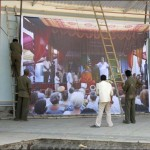 Baba&#039;s darshan photo is raised into position at the Amphitheatre Stage.jpg
